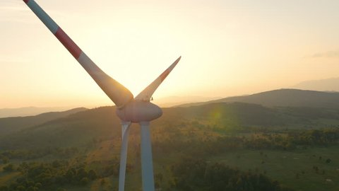Aerial - Wind turbine blocking the sun with propeller at sunset
