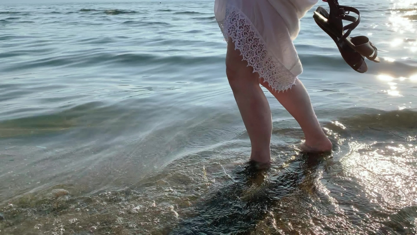 Young blond woman walking on the beach barefoot 4k #1033819298