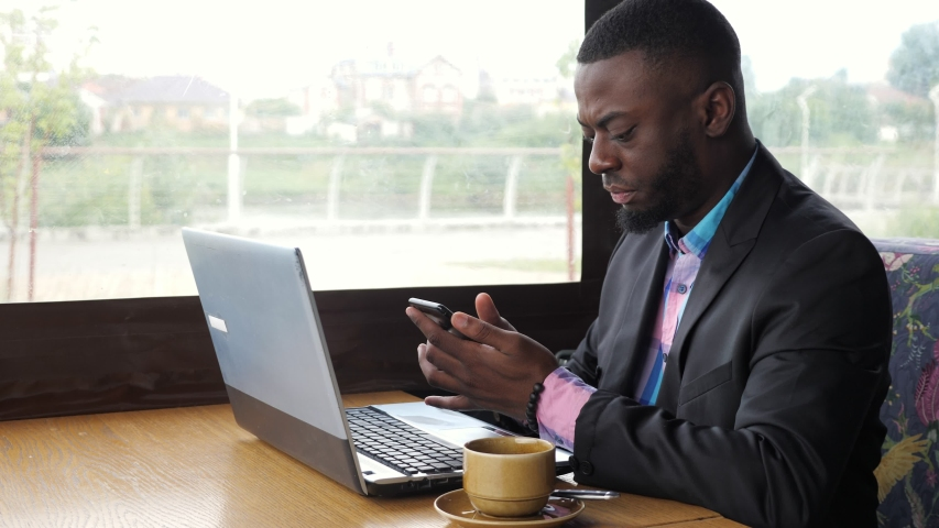 Afro american man has breakfast. Black businessman works on laptop with smartphone in cafe and drinks coffee. He types on computer looking at mobile phone screen. Wears in shirt and suit jacket.   Shutterstock HD Video #1033868528