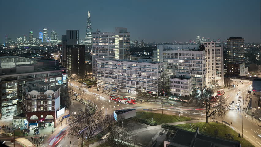 An HD timelapse of evening traffic flowing around a roundabout in South London, with the skyline of the city behind. Another version with more ambient light and less city lights is also available.