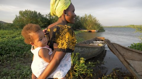 A slow motion shot orbiting around an african woman with her baby on her  back next to fishing boats on lake victoria