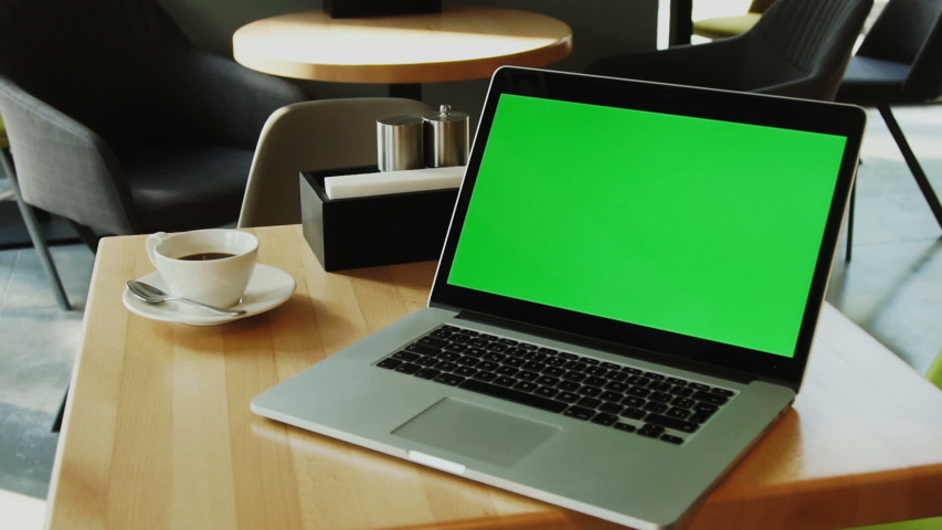 Laptop with chroma key screen on the wooden table with cup of coffee behind in modern cafe, green computer | Shutterstock HD Video #1033933928