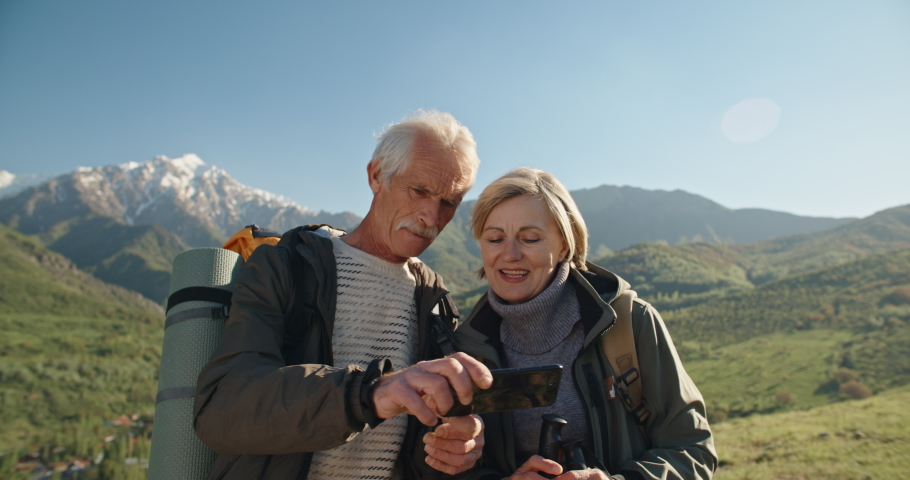 Old couple having a hike in spring mountains, then stopping to take a picture on a smartphone. Senior caucasian family spending time together travelling after retirement - tourism concept 4k #1034041928