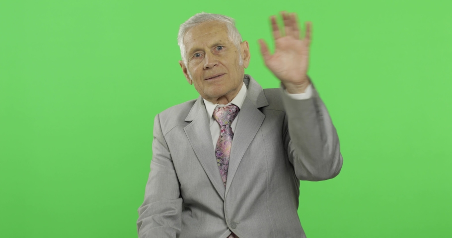 Elderly businessman waving with hands to camera. Old man in formal wear on chroma key background. Place for your logo or text. Green screen background | Shutterstock HD Video #1034085668