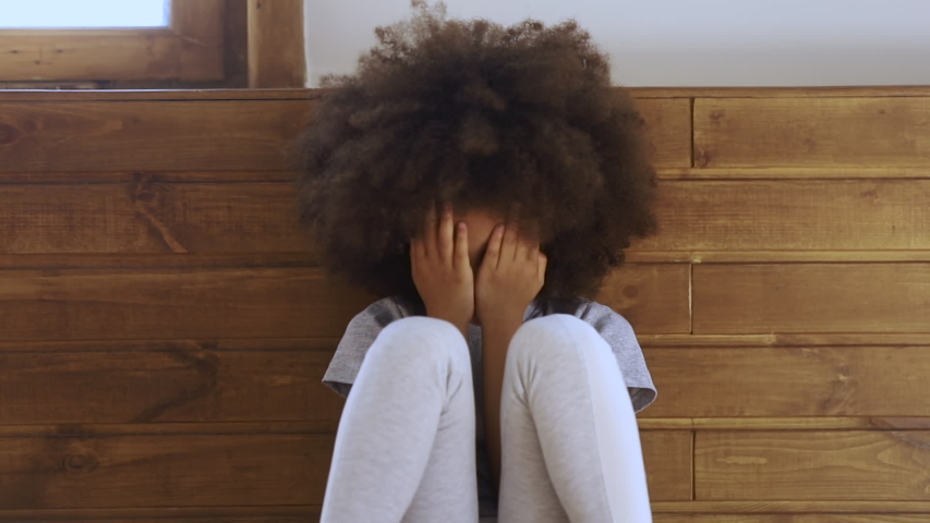 Upset little african american preschool kid girl crying alone feeling bullied abused abandoned, sad offended lonely black child stressed or scared sitting on floor, children problems concept
