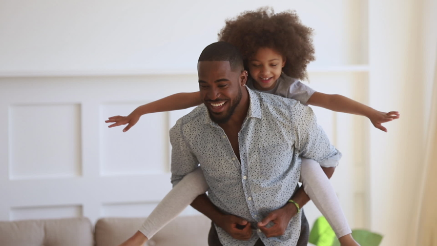 Happy family loving black dad giving cute little funny kid daughter piggyback ride spinning at home, cheerful african father carrying small child girl on back bonding having fun playing together