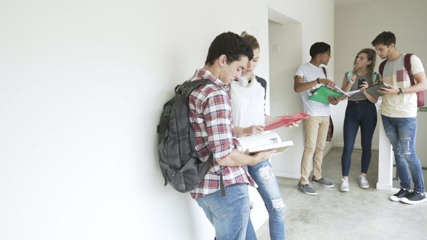 Point of view shot of college students reading book and using digital tablet while standing in the corridor | Shutterstock HD Video #1034130848