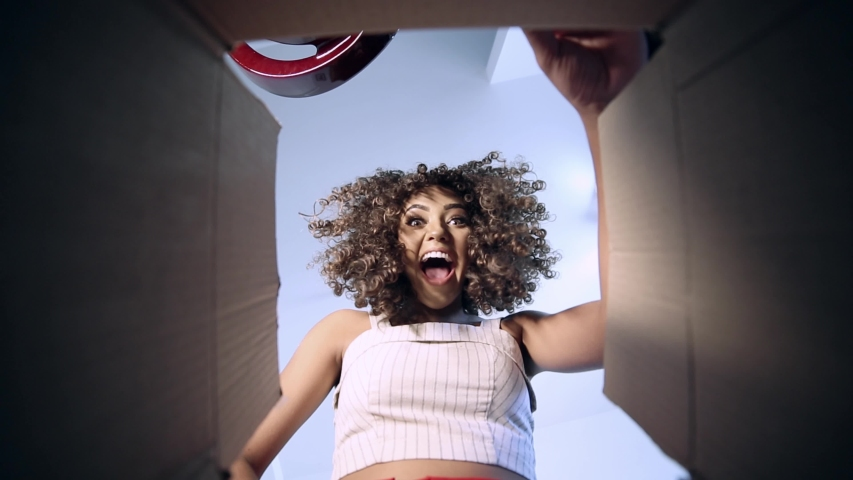 Beautiful brunette with curly hair opening the box with your order received by the post office or courier company. Brazilian young woman receiving order. | Shutterstock HD Video #1034134328