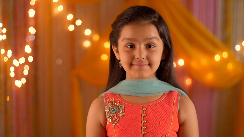 Young girl wearing salwar kameez smiling at the screen - Headshot. HD video clip of a smiling girl - wearing ethnic clothes for puja at home. Colorful festive background with lights