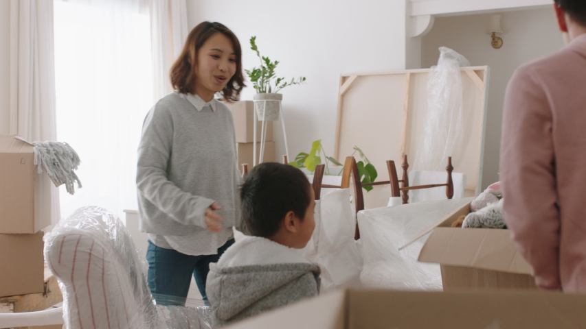 Happy asian family moving into new home owners with children helping parents move into house carrying boxes enjoying teamwork together with kids real estate property investment 4k footage | Shutterstock HD Video #1034208488