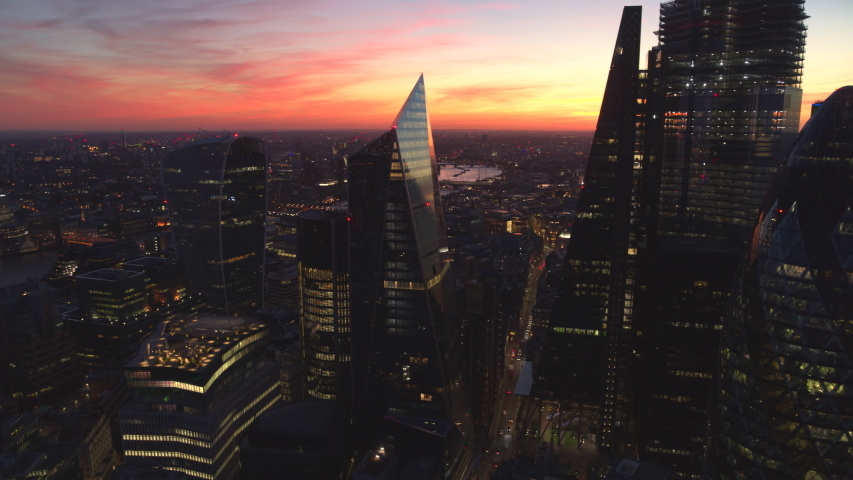 LONDON, UK - SEPTEMBER 9 , 2018: Aerial night view of London City on September 09 , 2018 in London, England. Aerial stock footage looking at over Tower Bridge, The Shard and The Gherkin