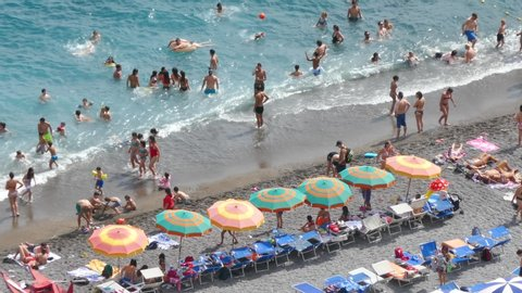 Positano, Italy, July 2019: Aerial view of sandy beach with rows of colorful umbrellas, swimming people in sea bay with transparent blue water in summer. Amalfi coast Italy