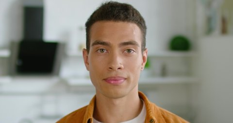 Portrait of young confident Hispanic man, close up, smiling, looking at camera, optimistic, decisive, healthy, handsome, enjoying his life, dark brown hair, brown eyes, Latin. 4K, shot on RED camera.