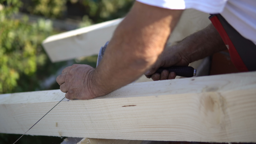 Builder nailing nails with hammer at work with wooden roof construction  | Shutterstock HD Video #1034262578