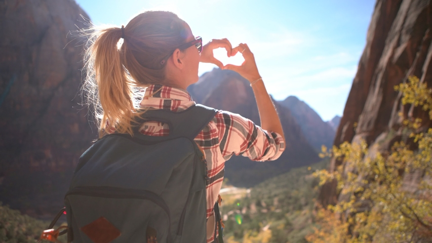 Young woman on top of mountain making heart shape finger frame with hands loving nature and embracing environment; Hiking girl enjoying outdoor activities  | Shutterstock HD Video #1034291318
