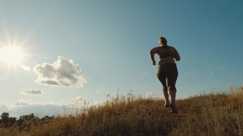 Rear view: Young plus size girl runs up the hill in the early morning. Concept of losing weight with exercise for health. Slow-motion shot