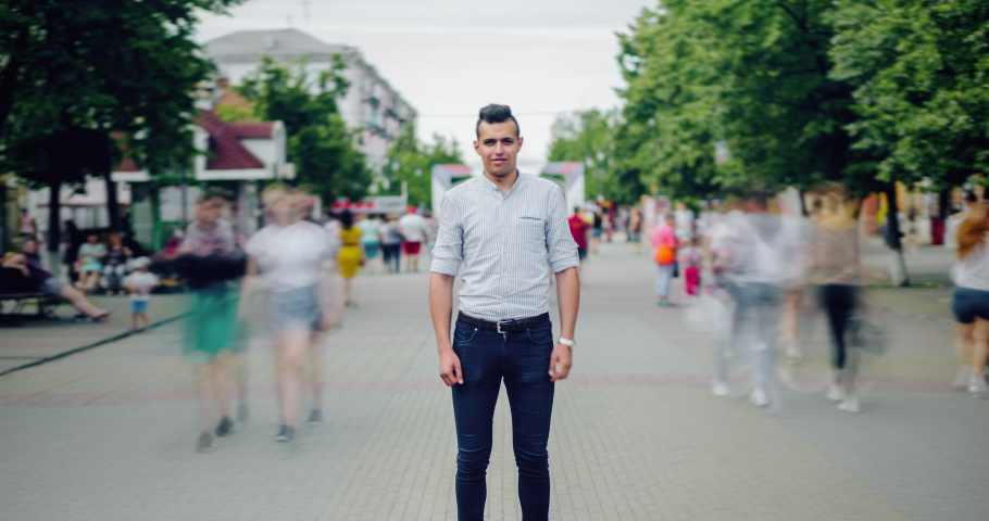 Zoom in time lapse portrait of Arabian student standing in street among flow of people looking at camera with serious face. Youth, modern life and summer concept.