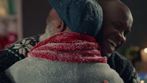 african american grandparents visiting for christmas hugging family giving presents enjoying festive holiday celebration on winter evening at home 4k footage