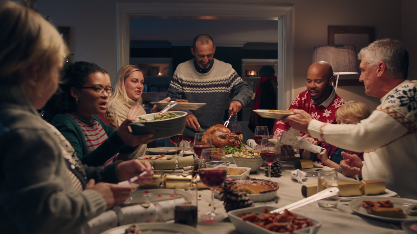 Family christmas dinner man cutting turkey serving delicious meal at festive celebration people sitting at table enjoying delicious feast celebrating holiday at home 4k footage | Shutterstock HD Video #1034495678
