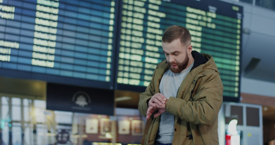 Young Caucasian guy with a beard arriving from a trip to the airport and walking through the arrival hall, then young pretty girlfriend meeting him and hugging tight. | Shutterstock HD Video #1034506958