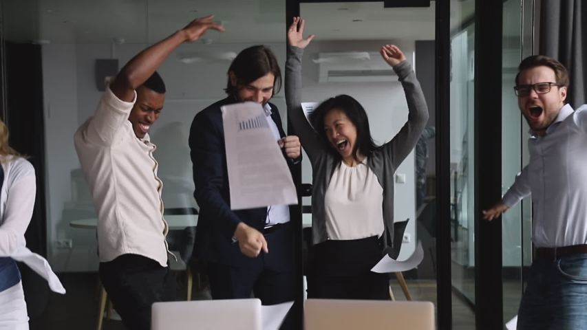 Happy successful multinational business team people dancing tossing papers celebrate success at corporate party, overjoyed excited motivated diverse colleagues group enjoy victory dance in office