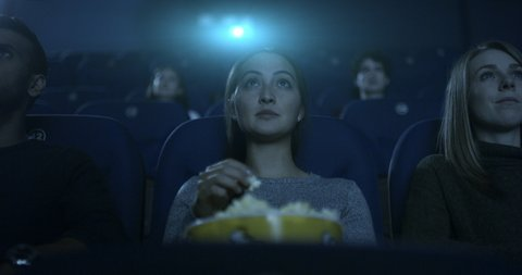 Young woman sitting in a movie theatre watching a movie, eating popcorn