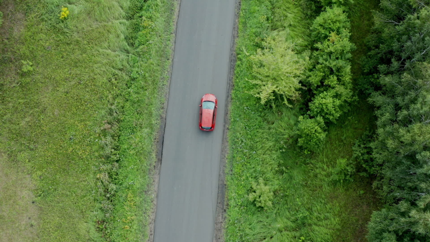 Aerial view of a red car driving on country road | Shutterstock HD Video #1034676668