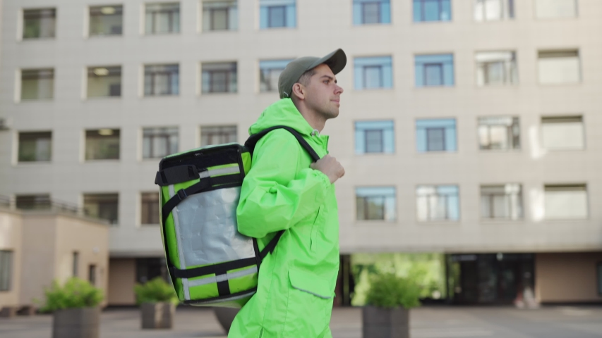 Side view waist up tacking shot of young delivery man in green uniform and cap walking down street with insulated backpack delivering food | Shutterstock HD Video #1034703518