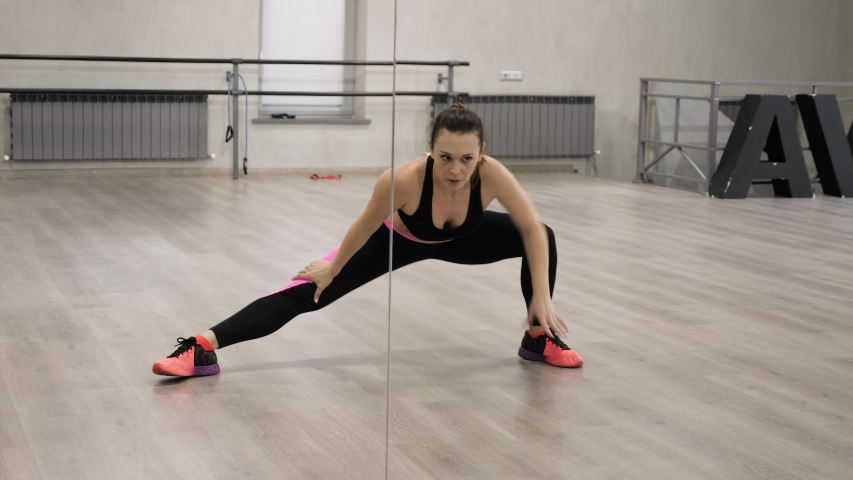 pretty lady in black and pink sportswear warms up and stretches body reflecting in huge gym mirror #1034722418