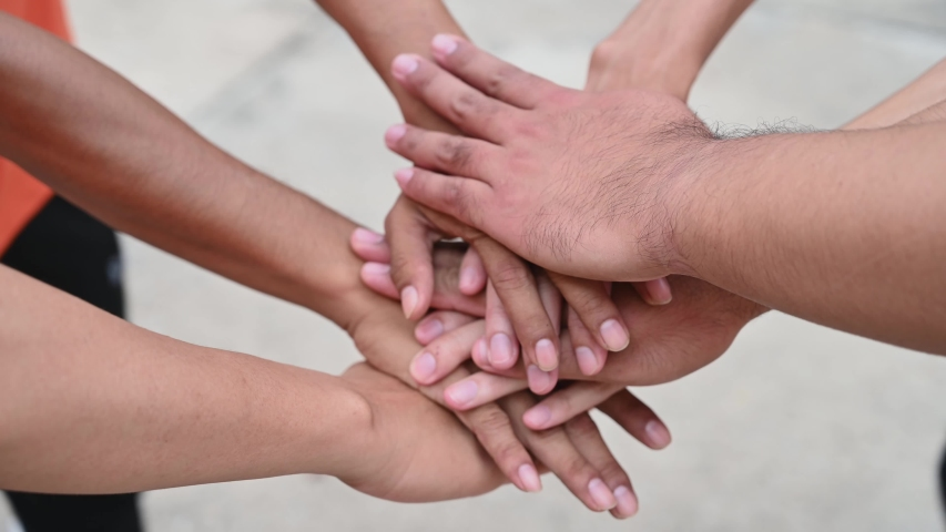 A group of friends extended their arms to touch their hands for unity. | Shutterstock HD Video #1034748128
