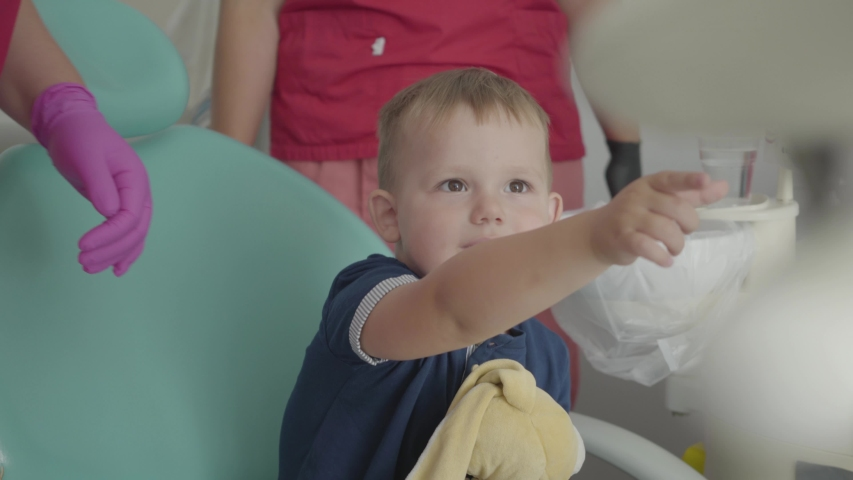 Adorable small boy playing with medical tools sitting in the chair in the dentist office. Carefree child visiting doctor. Boy plays at the dentist. Dental treatment, medical concept. Dental care. | Shutterstock HD Video #1034842358