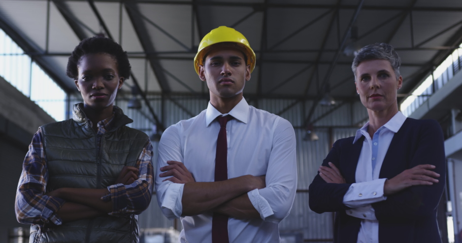 Close up low angle portrait of a young African American female warehouse worker, a young Asian male and a middle aged Caucasian female warehouse manager, looking straight to camera and crossing their #1034853578