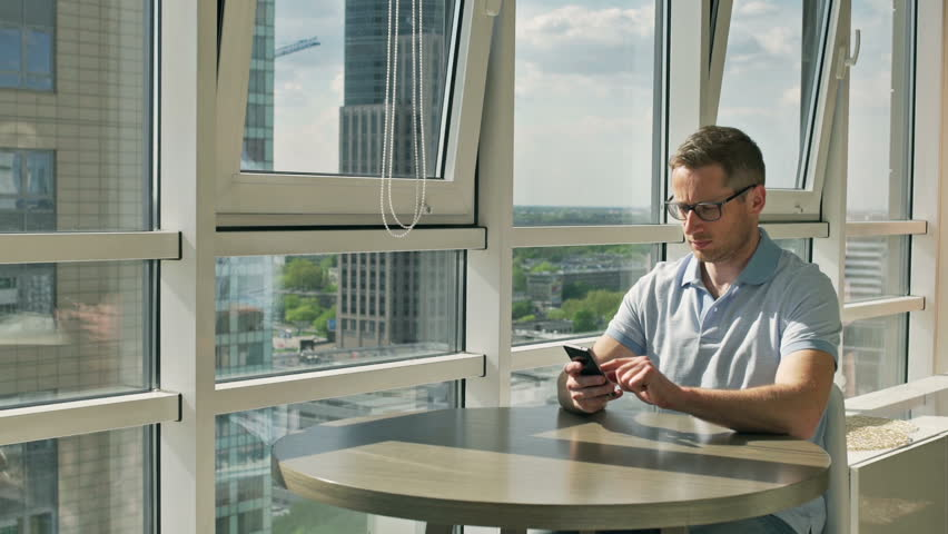Man sitting at the table and talking on cellphone