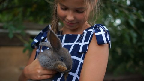 Happy childhood. Close portrait of a girl with a rabbit. The child gently hugs a gray fluffy rabbit, rabbit farm