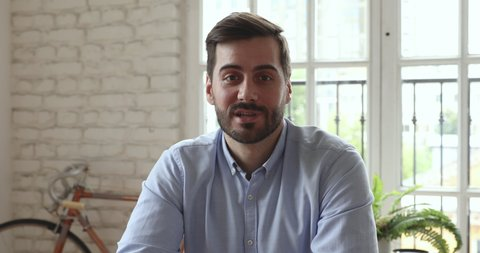 Confident businessman business coach speak look at camera in office, male entrepreneur talk during conference online call job interview recording online training webinar videoconference, webcam view