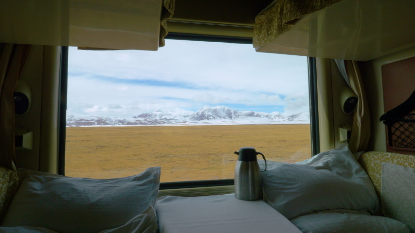 CLOSE UP: Stunning view of the snowy Himalaya from the comfort of a first class overnight train. Two soft beds in a sleeper cabin lay empty as the fast train crosses the scenic Tibetan landscape. | Shutterstock HD Video #1035233498