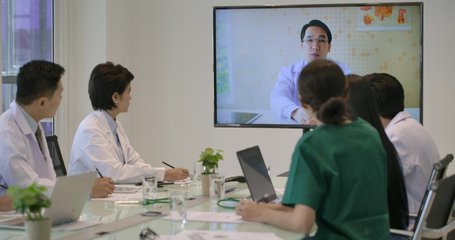 Medical team having an online video conference in meeting room at hospital.