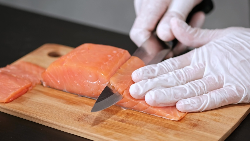 A young male sushi chef cuts a smoked salmon filet with a knife on a table. Hands in gloves close-up, gray background. | Shutterstock HD Video #1035312128