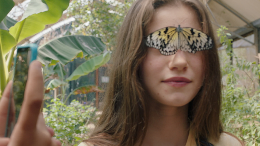 Beautiful butterfly on girls face with happy friend taking photo using smartphone friends having fun in zoo wildlife sanctuary sharing nature excursion on social media 4k footage | Shutterstock HD Video #1035354518