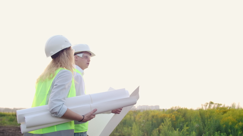 A man and a woman builders with drawings in white helmets go and talk on the construction site | Shutterstock HD Video #1035355328