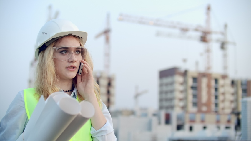 Portrait of a woman engineer in a helmet talking on the phone on the background of construction with cranes holding drawings in his hands. Female engineer on construction site | Shutterstock HD Video #1035360368