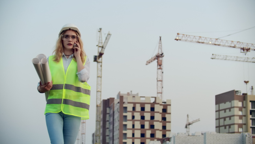 Dialogue on the phone a woman in a helmet on the background of construction discusses with the Director of the construction site of the building | Shutterstock HD Video #1035360398