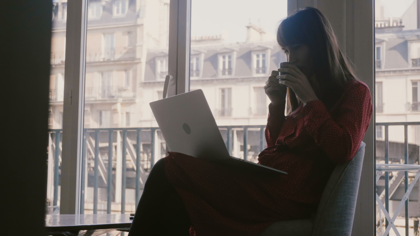 Beautiful relaxed young businesswoman using laptop and smartphone, drinking coffee at large apartment window in Paris. | Shutterstock HD Video #1035394238