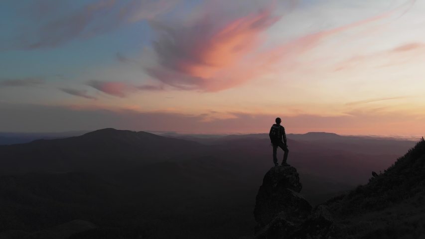 Person standing on rock with epic mountain viewpoint with a colorful sunset drone aerial landscape shot #1035432278