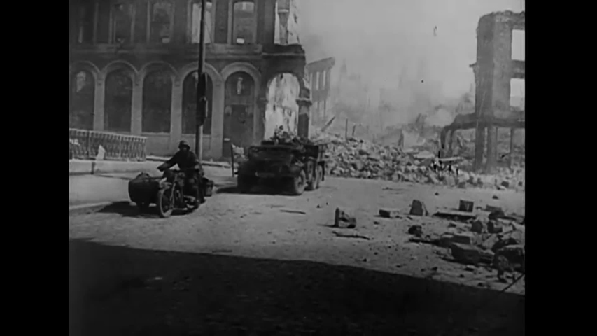 CIRCA 1940 - German soldiers drive trucks and tanks through the wreckage of a city they destroyed.