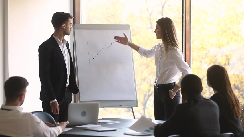 Company head and business trainer stands in front of audience diverse staff members making presentation using flip chart raised sales positive results of work done, seminar corporate education concept | Shutterstock HD Video #1035500018