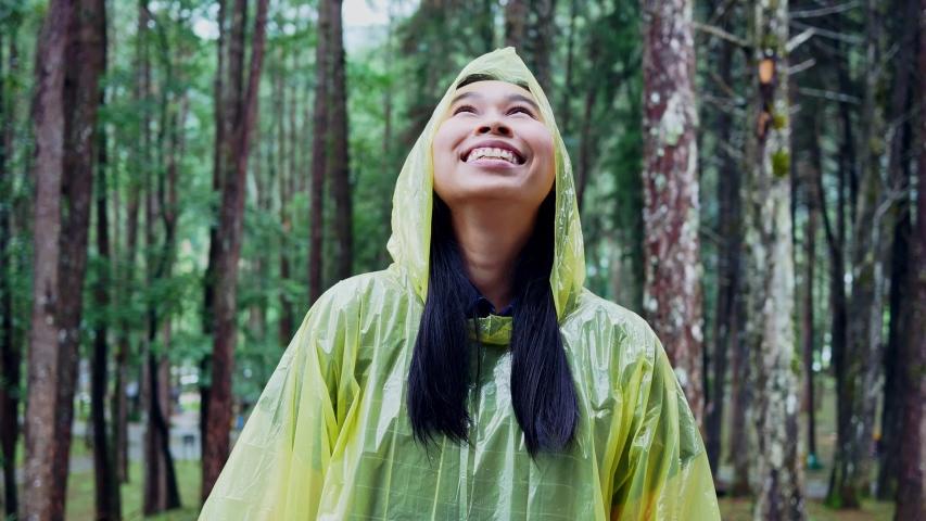 Portrait of Happy Asian woman wearing yellow raincoat stand in rain. #1035504308