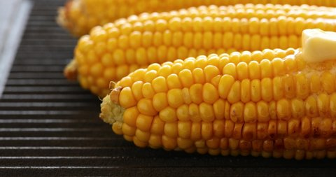 Melting butter on hot corn,  corn on the cob with butter and  salt  on the grill plate, close-up,4k