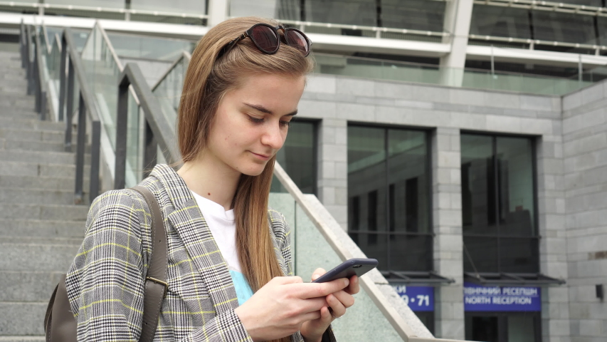 Happy Girl Chatting on the Smartphone Near Modern High Tech Building, Office | Shutterstock HD Video #1035514148