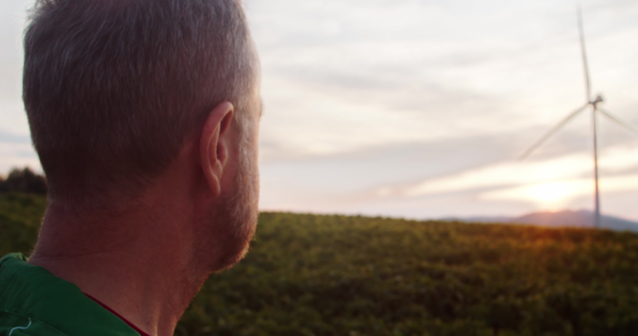 Back close-up of elder farmer looking at sunset in gorgeous green farmland with windmills. Alternative electricity wind turbines spinning. Ecology concept.   Shutterstock HD Video #1035557618